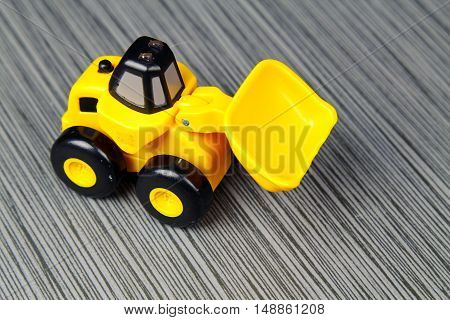 A yellow toy truck on a grey stone background with cpy space selective focus