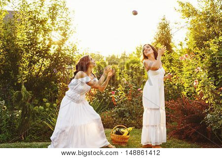 Two cute sisters in long white dresses and a basket with harvest. She catches eggplant. Ripe fruits and vegetables. A bountiful harvest. Agriculture. The setting sun. Soft focus