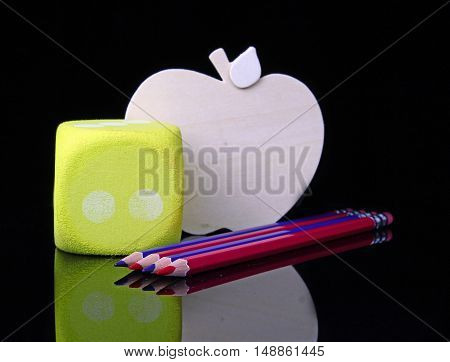 Blue and red pencils with an apple cutout on a black background for the back to school theme.