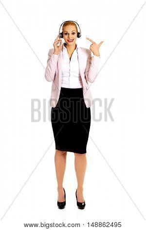 Happy female phone operator pointing at headphones