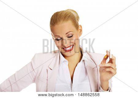 Happy business woman holding broken cigarette