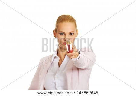 Attractive business woman pointing on camera with oversized pen