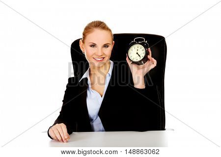 Happy business woman with alarm clock behind the desk