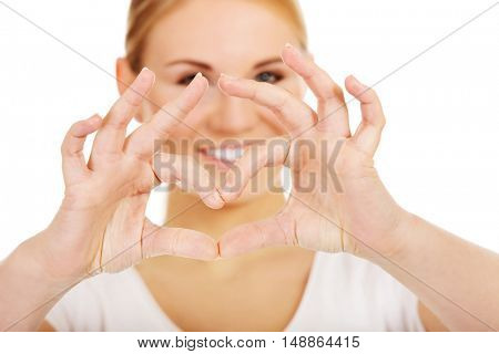 Young woman making heart shape with her hands