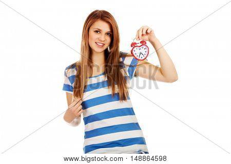 Teenage woman holding alarm clock