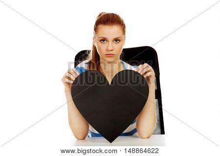 Worried teenage woman holding black paper heart