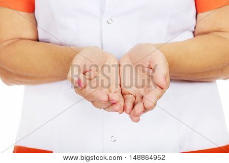 Elderly female doctor or nurse presenting something on open palms