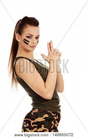 Young beautiful soldier woman doing gun gesture