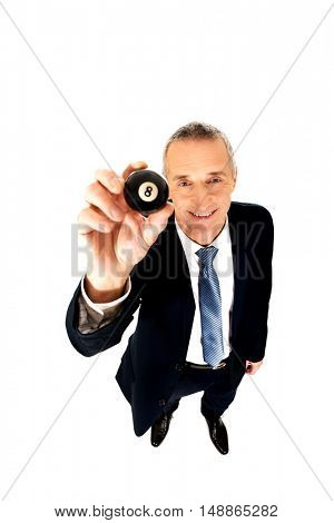 Businessman holding black billiard ball