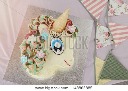 homemade rainbow unicorn cake with vintage bunting toning