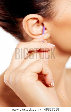 Brunette woman cleaning her ear.