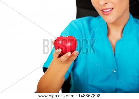 Young female doctor holding toy heart