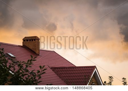 The red roof of the house on a background of strong clouds and setting sun.