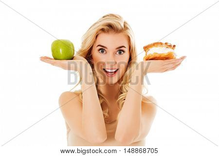 Young woman holding an apple and cookie