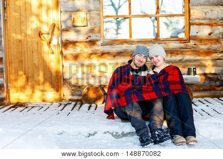 Couple outdoors on beautiful winter day in front of log cabin vacation house