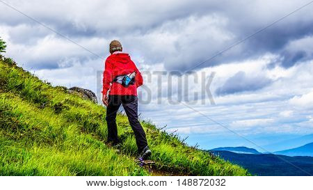 Senior woman in a red jacket hiking up a steep slope on Tod Mountain at the village of Sun Peaks in the Shuswap Highlands of British Columbia, Canada