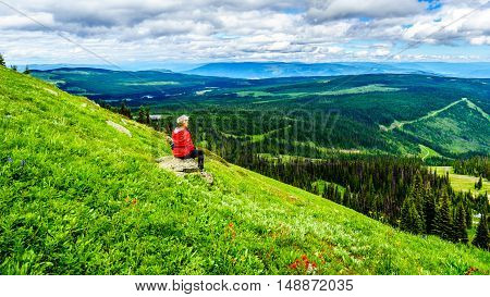 Senior woman enjoying the view of Sun Peaks valley during a hike on Tod Mountain in the Shuswap Highlands in British Columbia, Canada