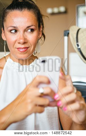 Portrait of beautiful adult woman holds smartphone in arm and looking away