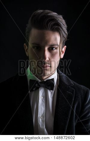 Young businessman confidently posing and looking at camera, wearing suit, on dark background
