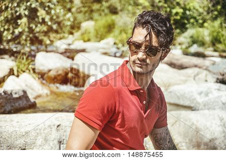 Attractive young man outdoor at river or water stream, sitting on big rock, looking away, with stones in background