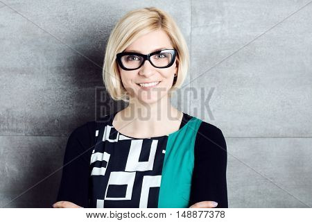 Closeup portrait of happy young woman standing by grey wall in glasses.