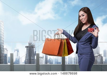 Pretty Asian Lady With Shopping Bags Showing Credit Card