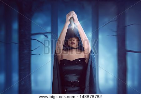 Witch Woman With Black Cloak Has Knife Held High And Is Ready To Stab