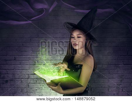 Asian Sexy Witch Creating A Spell At The Book