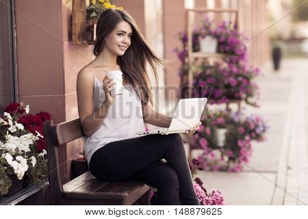 Portrait Of Smiling Young Woman Sitting On The Bench And Using Laptop Computer Outdoors. Urban Life Concept.