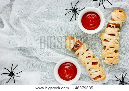Homemade sausage mummies with ketchup Halloween funny food recipe top view blank space for text