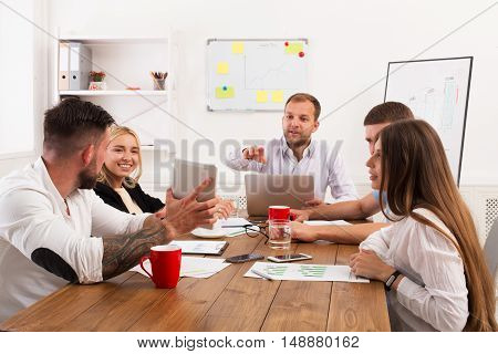 Business meeting. Young hipsters businessmen and women at modern office, team discussion at workplace, show information on tablet. Brainstorming and communication with partners for startup.