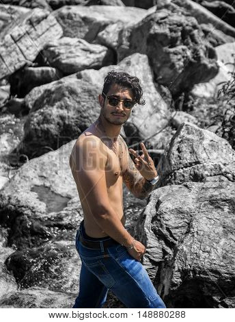 Athletic shirtless young man outdoor at river or water stream, looking away, with rocks and stones in background, doing Victory sign with fingers