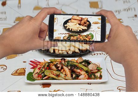 Using mobile phone to take photo a dish of fried basil with mixed vegetables served for share to social network. Selective focus.