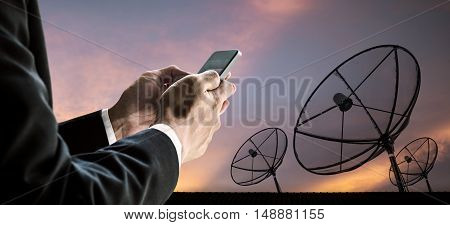 Businessman using smart phone, with silhouette telecoms satellite dish digital network and sunset sky