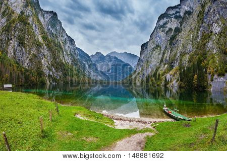 Fishing boats with a small engine in shallows of the lake. The magic blue lake Obersee in Bavarian Alps. Concept of active tourism and ecological tourism