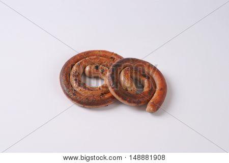 grilled spiral pork sausages on white background