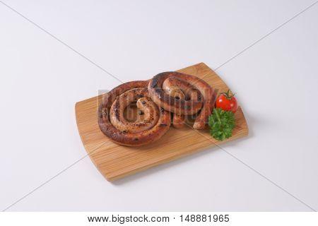 grilled spiral pork sausages on wooden cutting board