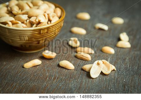 Roasted peeled salted peanuts in rustic bowl shallow focus