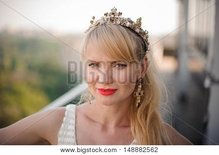 Beautiful blonde woman with long hair wearing crown decorated gemstones. outdoor