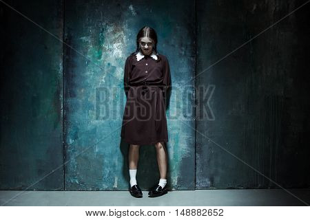 Halloween theme: Portrait of a young smiling girl in school uniform as killer woman against school board .