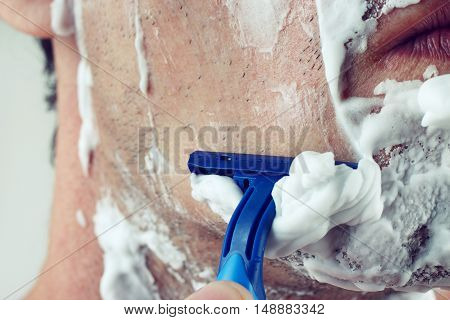 Young man with a razor shaving his cheek close up gently toned
