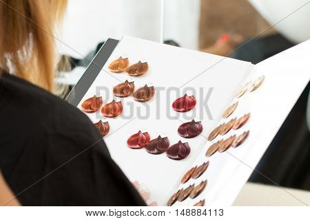 poster of Hairdresser salon visitor looking at the book of color samples close up. Visitor sitting at hair stylist office choosing new hair color. Haircare beautician dyeing or changing hair colour concept