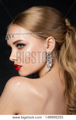Portrait of young beautiful woman with evening make up looking over her shoulder. Model posing over dark background. Red lips and eyeliner. Classic makeup concept. Studio shot.