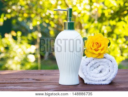 Soap dispenser and white towel. Fragrant yellow rose. Spa concept. Health and beauty. Body Lotion with rose oil. Natural green background. Green blur. Copy space.