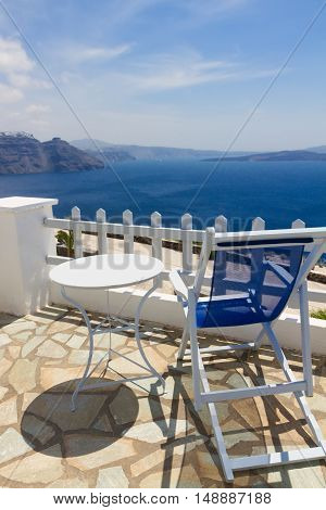 relaxing blue chair withwhite table and view of caldera, Santorini, Greece