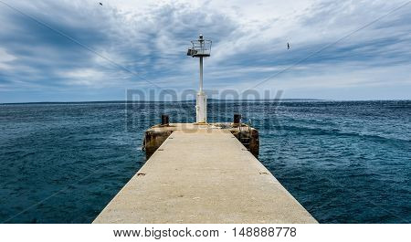Old pier with a lighthouse beacon and calm sea. Rusty moorings on concrete pier on a windy day with dramatic clouds. Adriatic sea - Silba Croatia.