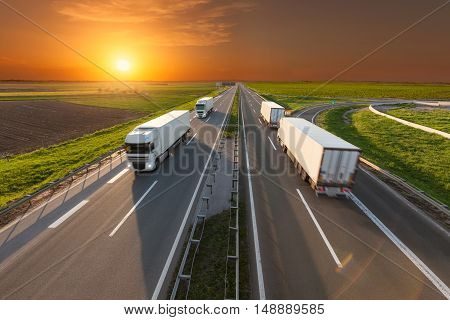 Many delivery trucks driving through agricultural fields. Fast blurred motion drive on the freeway at beautiful sunset. Freight scene on the motorway near Belgrade Serbia.