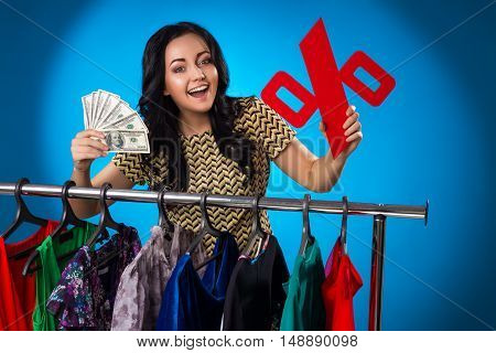 Happy Woman Holding Percent Sign And Hundred-Dollar Bills Under The Clothing Rack With Dresses On Blue Background