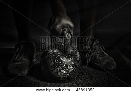 Sport. Unrecognizable strong athlete is going to do exercise with weight -- selective focus desaturated