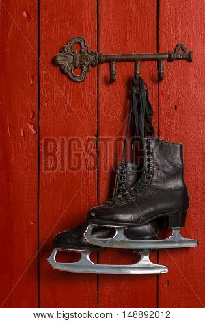 Old Black Figure Ice Skates Hanging On A Red Wooden Wall